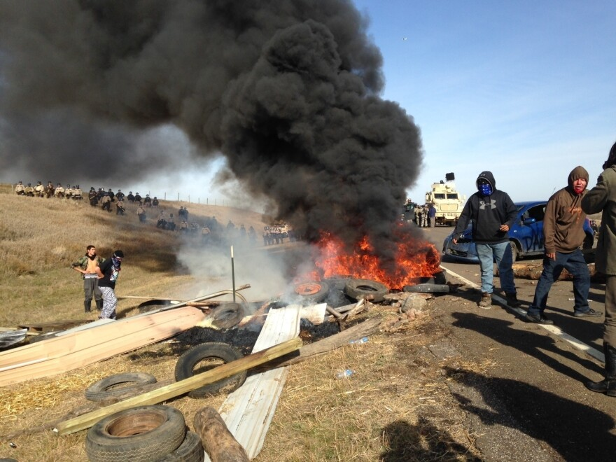 Dakota Access oil pipeline protesters burn debris as officers close in to force them from a camp on private land in the path of pipeline construction on Thursday.