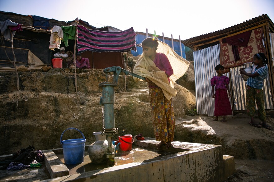 Sanura Begum collects water from a communal pump near her shelter in the Kutupalong Rohingya refugee camp in Bangladesh. Back in Myanmar, she says her family had their own well on their farm.