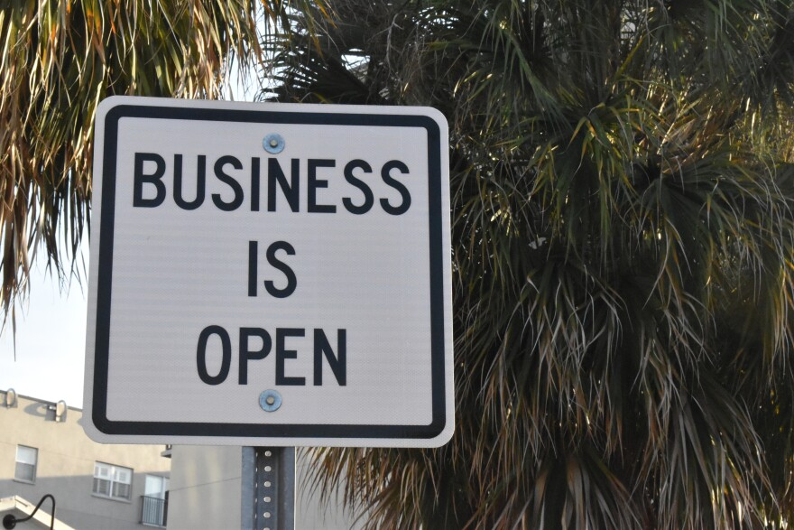 """A white sign says """"business is open"""""""