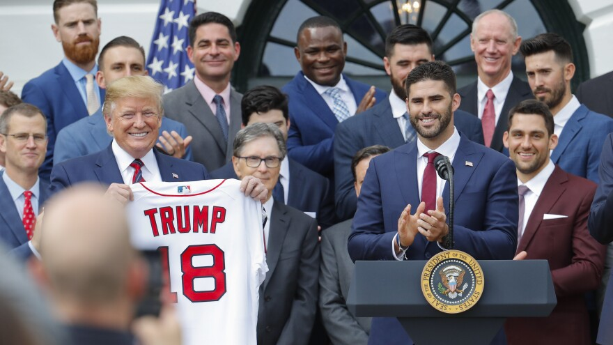 President Trump holds up a Red Sox team jersey that was presented to him by outfielder J.D. Martinez Thursday at the White House.