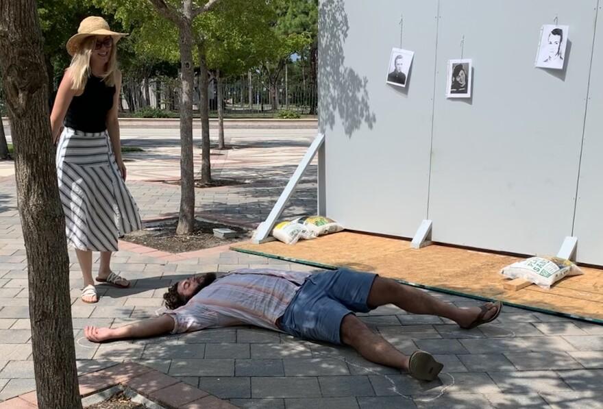 Professor Lauren Hansen stands after drawing a chalk outline around student Noah Opalsky.