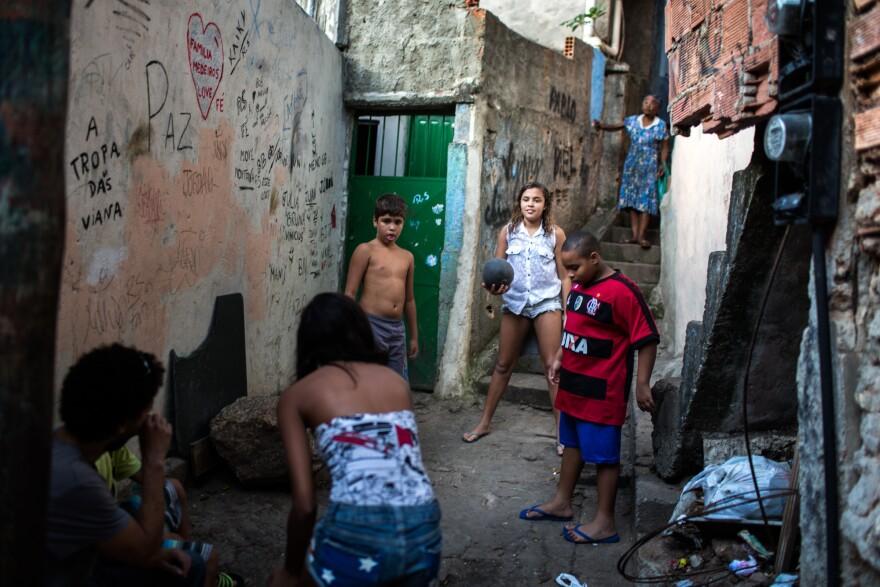 Lala (center) and Milena (back to camera) play a pickup game of soccer in their neighborhood, the Rocinha <em>favela,</em> a shantytown in Rio de Janeiro.