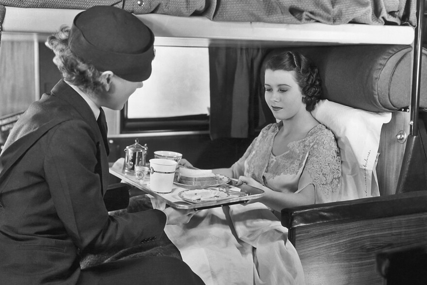 <strong>The good old days: </strong>A flight attendant serves coffee and sandwiches to a passenger on board an American Airlines flight, circa 1935.