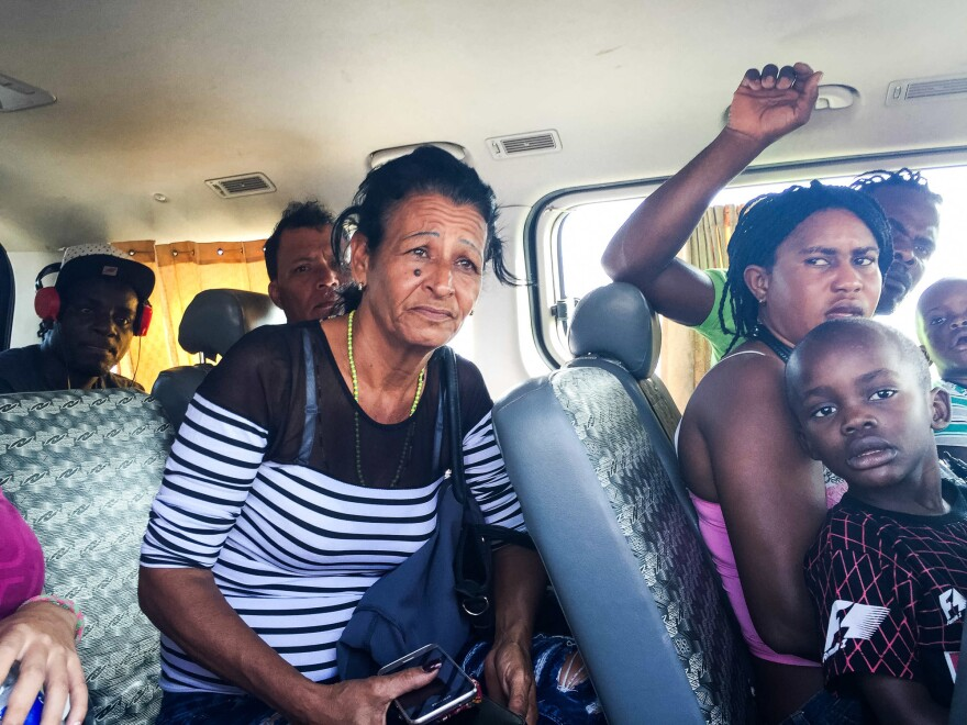 Marta sits in a van with migrants from Haiti after being detained by Peruvian migration officials. When the head officer took a liking to Liset, he decided to let them go and released the group.