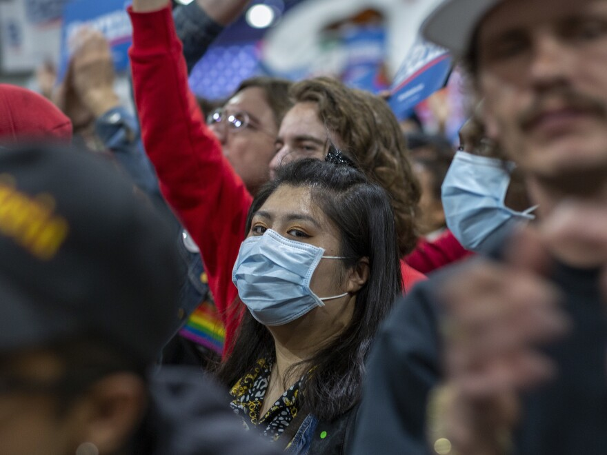 A woman in California wears a medical mask during a political campaign rally.