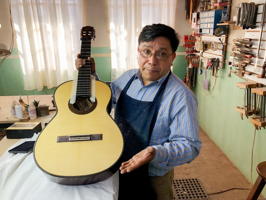 Master guitar maker Arnulfo Rubio Orozco holds up a recent project. It took him a month to craft this guitar with pearl accents and wood from southern Mexico.