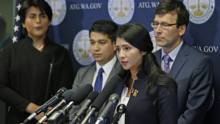Faride Cuevas, a participant in the Deferred Action for Childhood Arrivals, or DACA, program, talks to reporters Wednesday in Seattle as Washington Attorney General Bob Ferguson and other DACA participants look on.