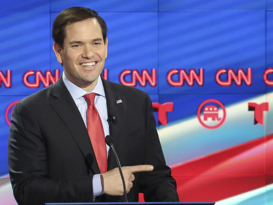 Florida Sen. Marco Rubio mockingly smiles and points toward Donald Trump during the last Republican presidential debate before Super Tuesday. Rubio hopes to pick off some states.