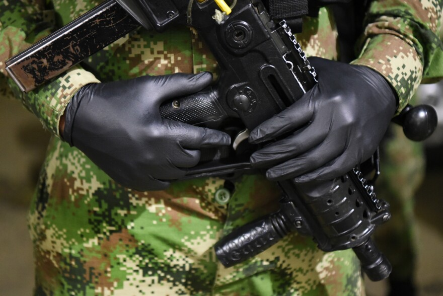 A soldier wears gloves to protect against the coronavirus on an army patrol of the city during the government-mandated curfew. <em>March 26, 2020, Cali, Colombia.</em>