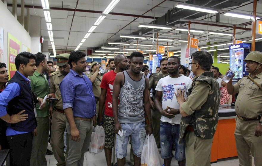 Indian police and onlookers surround African nationals at a shopping mall in Greater Noida.