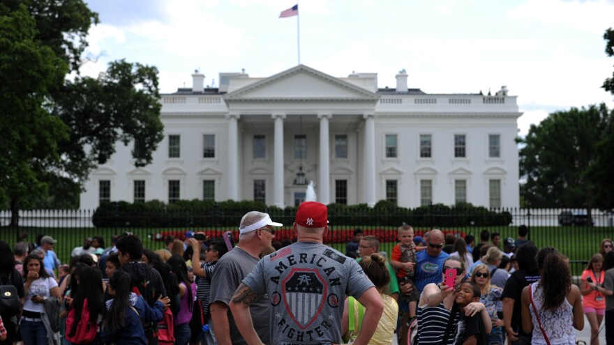 Tourists linger in front the White House in June.