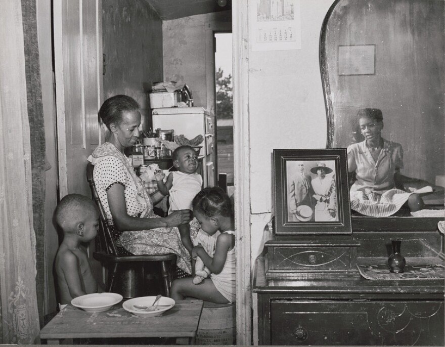 While working for the Farm Security Administration, Gordon Parks took this 1942 photo of Ella Watson at her home in Washington, D.C., with her three grandchildren and daughter.