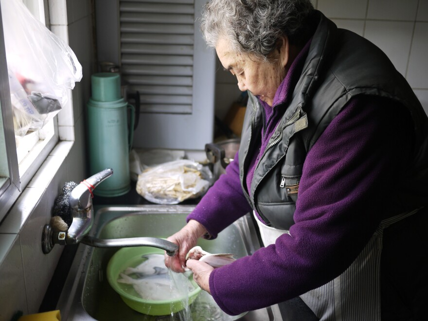Yuan Shuizhen, 85, prepares fish and chicken feet for the Lunar New Year holiday in her garden-level kitchen.