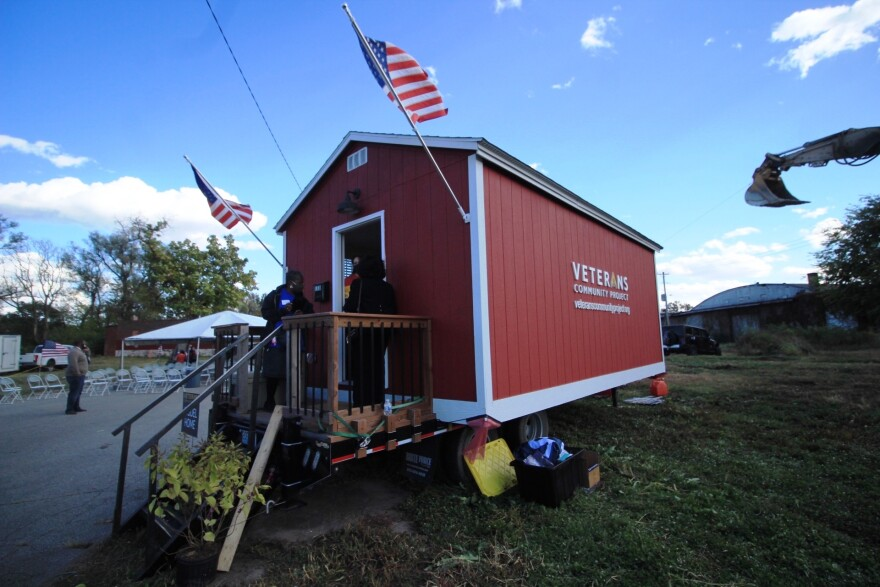 The image shows two women entering a small red building that says Veterans Community Project on the side. The door is flanked by two American flags. There is a backhoe in the right side of the photo.