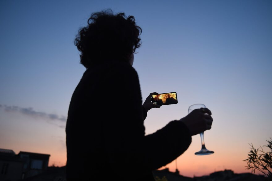 A woman drinks a glass of wine as she speaks and shares a drink with friends via a video call on March 26, 2020, in Bordeaux, southwestern France, in the evening on the tenth day of a lockdown aimed at curbing the spread of the COVID-19 (novel coronavirus) in France. (NICOLAS TUCAT/AFP via Getty Images)