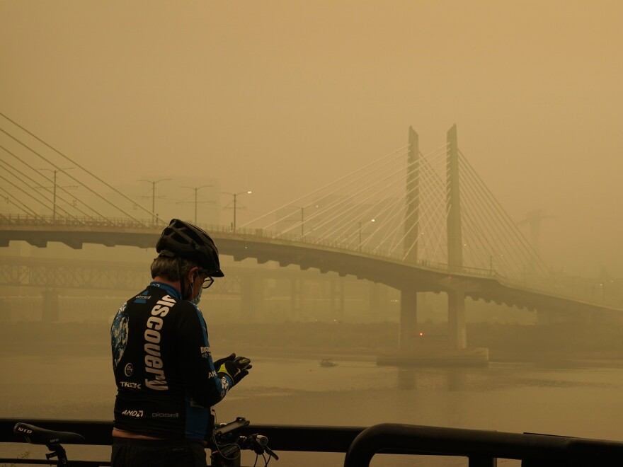 A man stops on his bike along the Willamette River as smoke from wildfires partially obscures the Tilikum Crossing Bridge on Saturday in Portland.