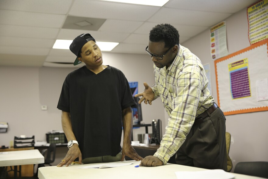 Carey helps a student in his GED class at the Youth Empowerment Project.