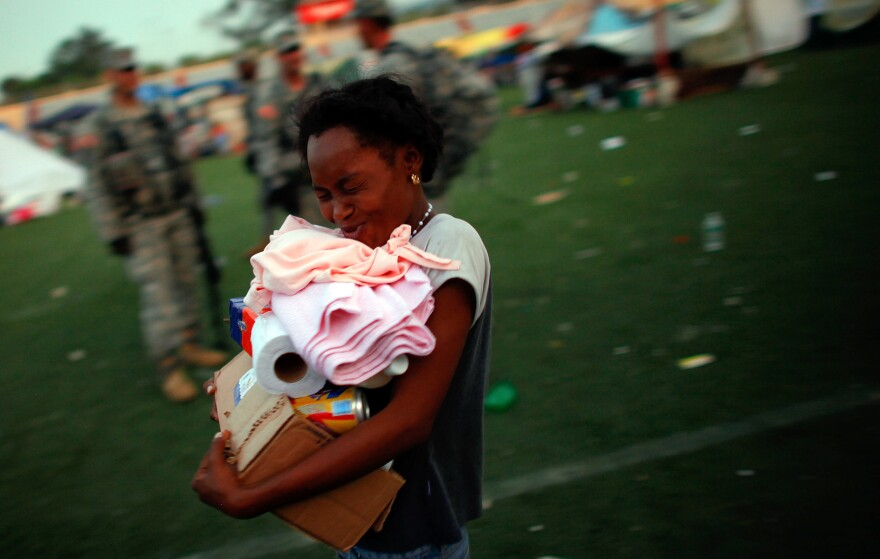 A Haitian woman smiles as she walks past soldiers from the 82nd Airborne after receiving her first ration of foreign aid, which has been coming in to a soccer stadium in Port-au-Prince, four days after the quake hit.