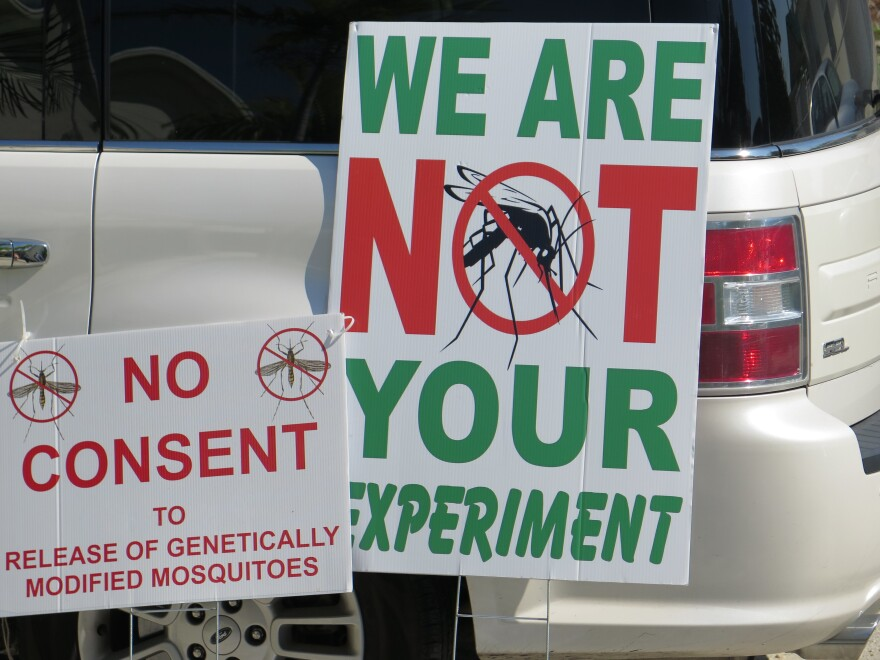 Protest signs at the Florida Keys Mosquito Control District board's meeting Saturday in Marathon, Fla.