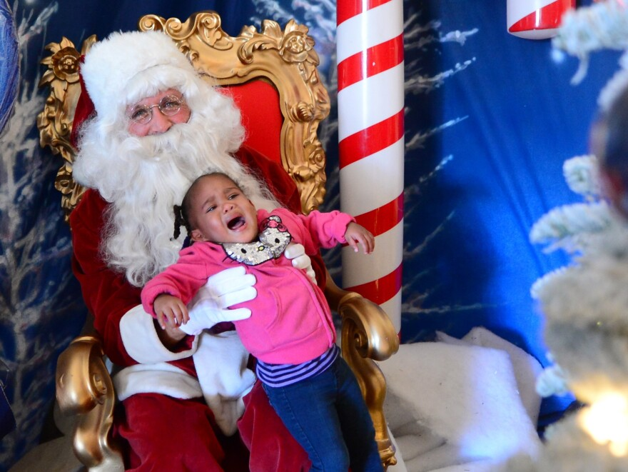 This toddler in Los Angeles cries for her mommy who placed her on Santa's lap.