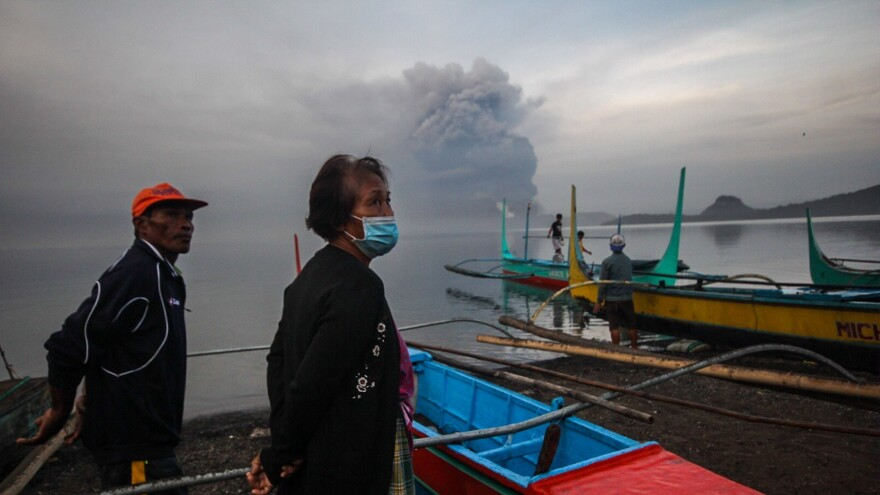 Villagers are seen as they look at Taal Volcano erupting in Batangas on Monday.