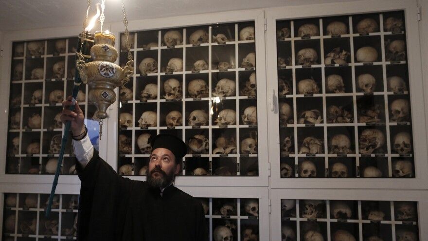 Greek Orthodox priest Apostolos Stavropoulos, 41, lights a torch inside the mausoleum in the village of Distomo in June 2013 on the eve of the 69th anniversary of the massacre committed by the Nazis during World War II. The remains of the more than 200 villagers killed, including women and children, are kept here.