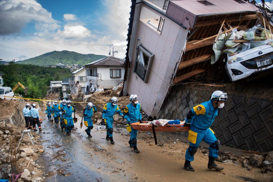 Police arrive to clear debris scattered on a street in a flood-hit area in Kumano, Hiroshima Prefecture, Japan, on July 9, 2018. (Martin Bureau/AFP/Getty Images)