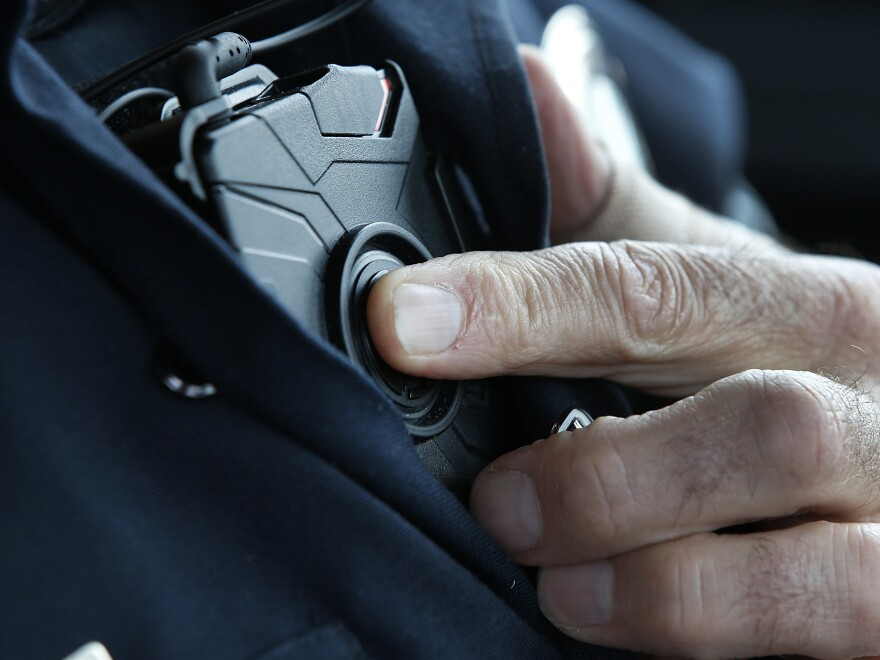 A patrol officer in West Valley City, Utah, starts a body camera recording by pressing a button on his chest in March 2015. The West Valley City Police Department issued 190 Axon Flex body cameras for all its sworn officers to wear.
