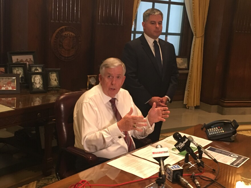 Gov. Mike Parson speaks to reporters with Department of Economic Development director Rob Dixon on May 14, 2019.