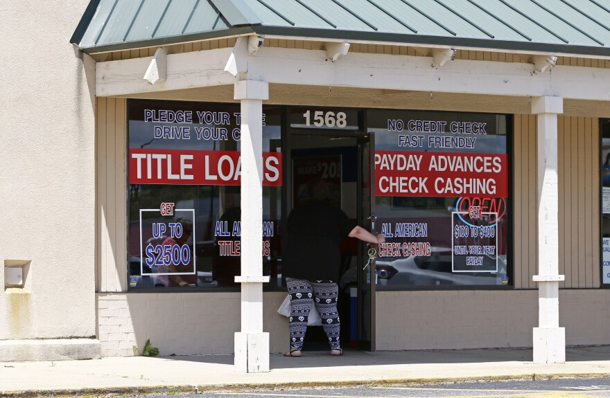 A woman enters an All American Check Cashing location in Brandon, Miss., on Friday, May 12, 2017. The windows of the storefront advertise payday advances, check cashing and title loans.