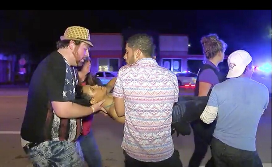 An injured person is escorted out of the Pulse nightclub after a shooting rampage June 12 in Orlando, Fla.