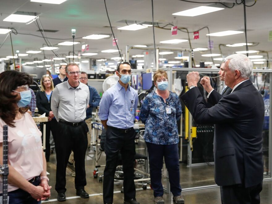 Pence talks with employees as he tours a GE ventilator plant in Madison, Wis.