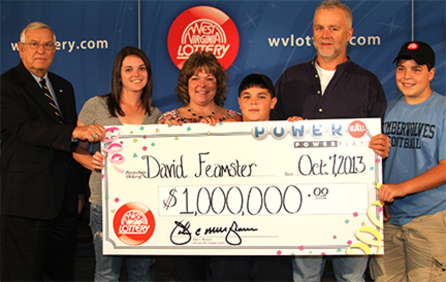 Commissioner John Musgrave presents check to David Feamster and family.