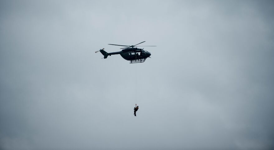 A helicopter carries an evacuee during the aftermath of Hurricane Harvey on Tuesday in Houston.