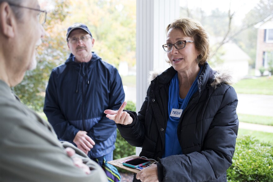 Trish Gunby speaks with a 99th district resident while knocking on doors on Saturday morning. Oct. 26, 2019