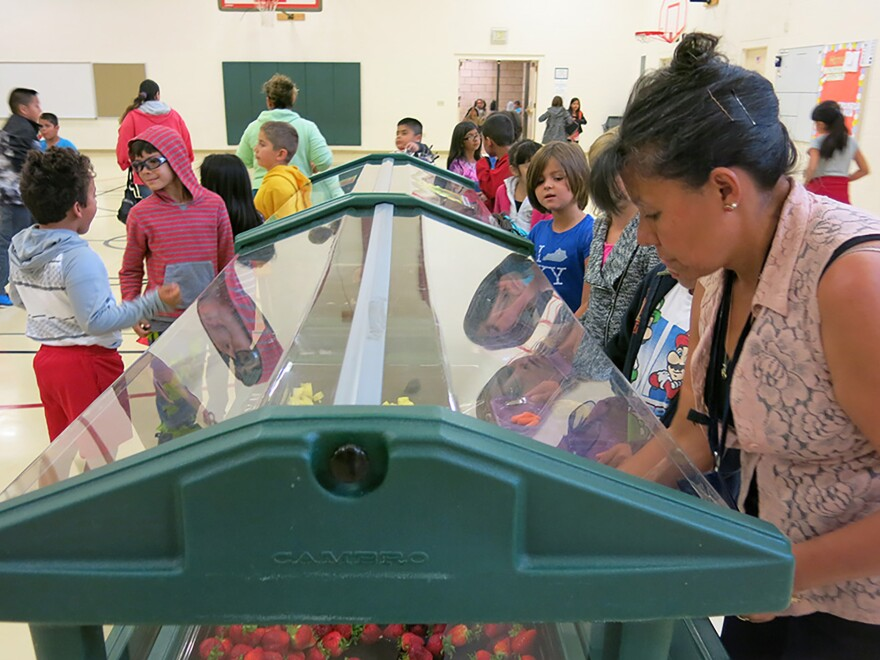 Gloria Restrepo, a teacher's assistant at Harris Bilingual Elementary School in Fort Collins, Colo., helps students choose their lunch.