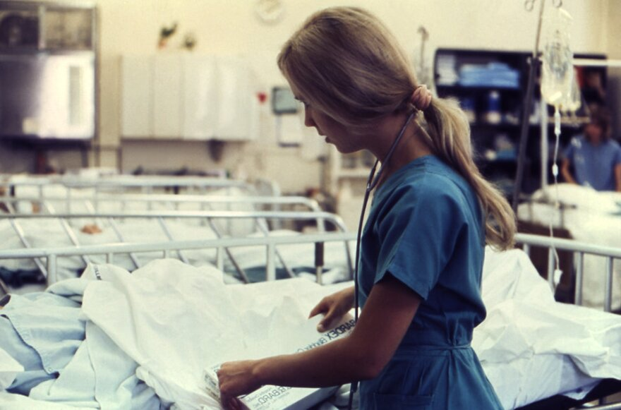 Lying atop a mobile gurney, a patient was being prepped and coached just prior to the subsequent medical procedure that was about to take place in this hospital setting. The nurse was wearing her requisite blue colored hospital scrubs, and had draped a st