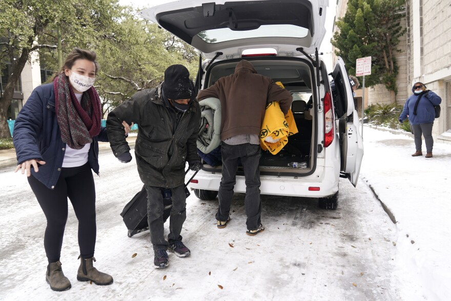 Three adults unloading small suitcases and blankets from a van on a snow and ice covered street.