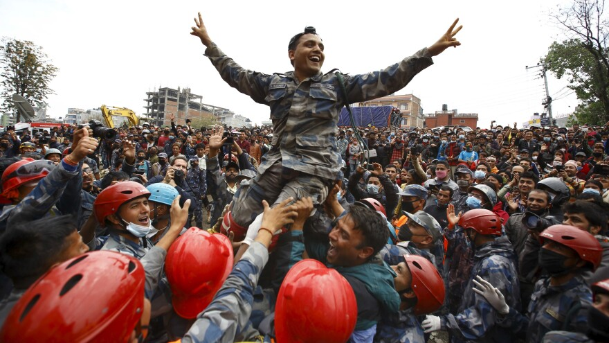 Members of Nepal's Armed Police Force carry an officer as they cheer the successful rescue of a teenager who had been trapped by Saturday's earthquake in Kathmandu.
