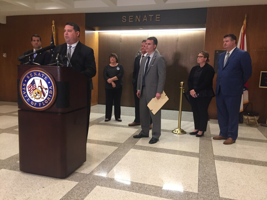 Florida Senator Travis Hutson (at podium) introduces a bill to give high school students an alternative path to graduation centered on vocational and technical training.