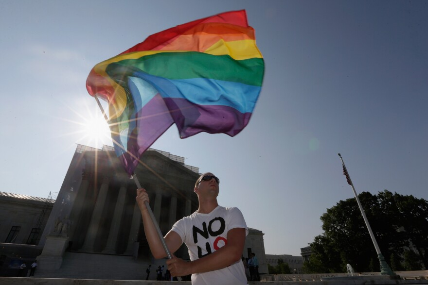 Gay rights activist Vin Testa of DC waves a flag outside the U.S. Supreme Court building on Tuesday in Washington, DC.