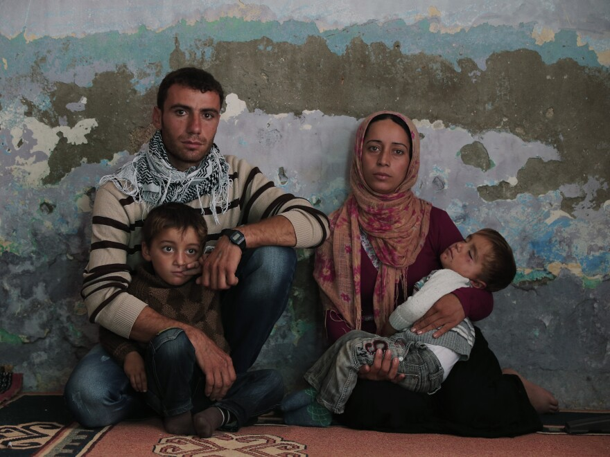 Syrian Kurdish fighter Delkhwaz Sheikh Ahmad, 22, sits with his wife Siham, 23, and their two sons, Dilyar and Ibrahim, at his brother's house on the Turkey-Syria border on Friday. He was preparing to leave for Kobani, Syria, to rejoin the fighting against the Islamic State.