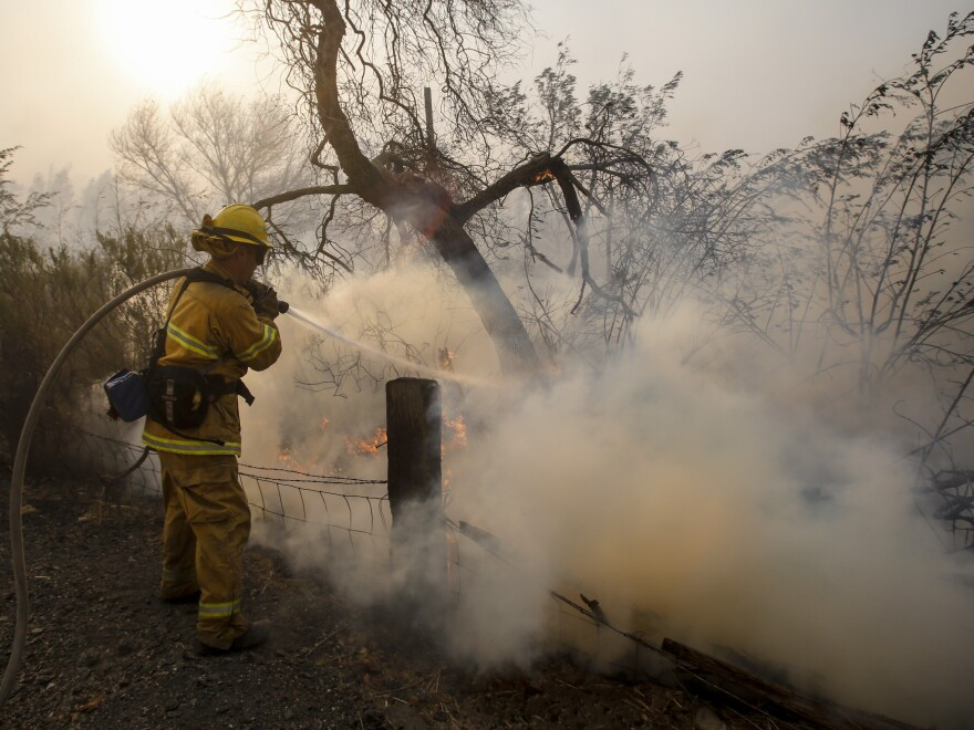 A firefighter battles a wildfire near a ranch in Simi Valley, Calif., on Wednesday. The large new wildfire erupted in wind-whipped Southern California, forcing the evacuation of the Ronald Reagan Presidential Library and nearby homes.