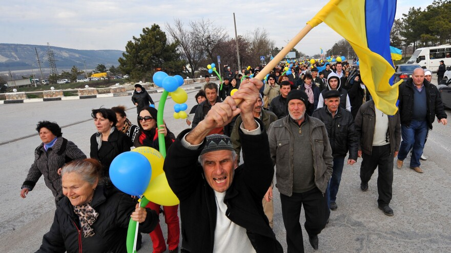 A member of the Crimean Tatar community holds the Ukrainian flag during a rally in front of a Ukrainian military base south of Simferopol, on Thursday.