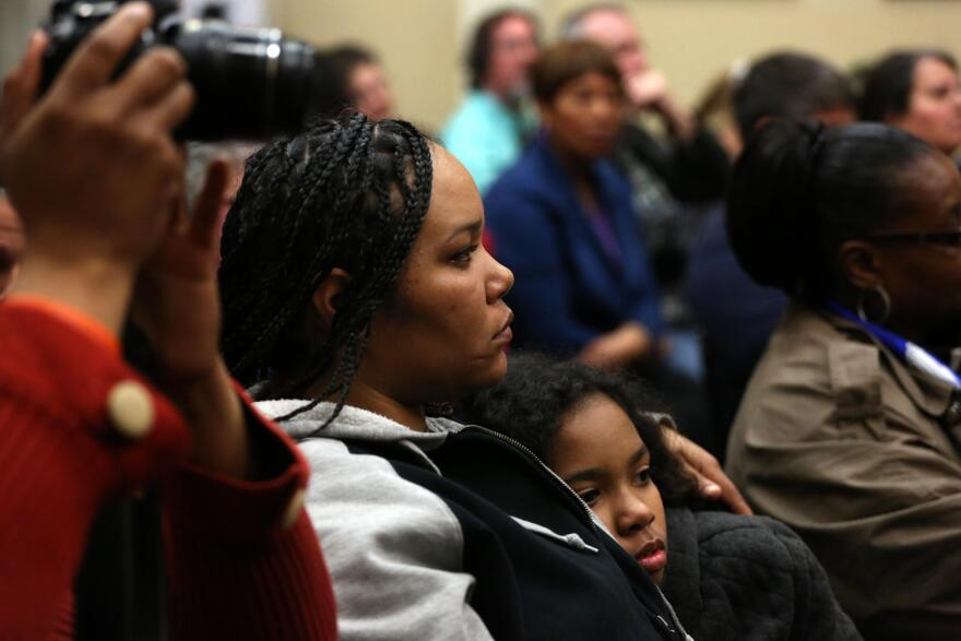 Ferguson residents Francesca Griffin and Mauraye Love, 9, listen as council members address audience questions.