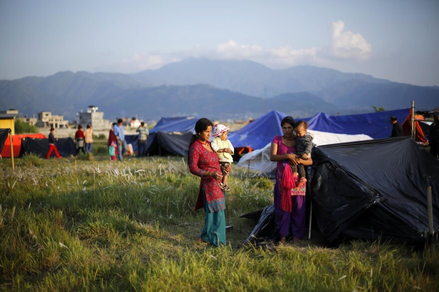 Displaced family members with their children in a field opposite the airport in Kathmandu on April 27.