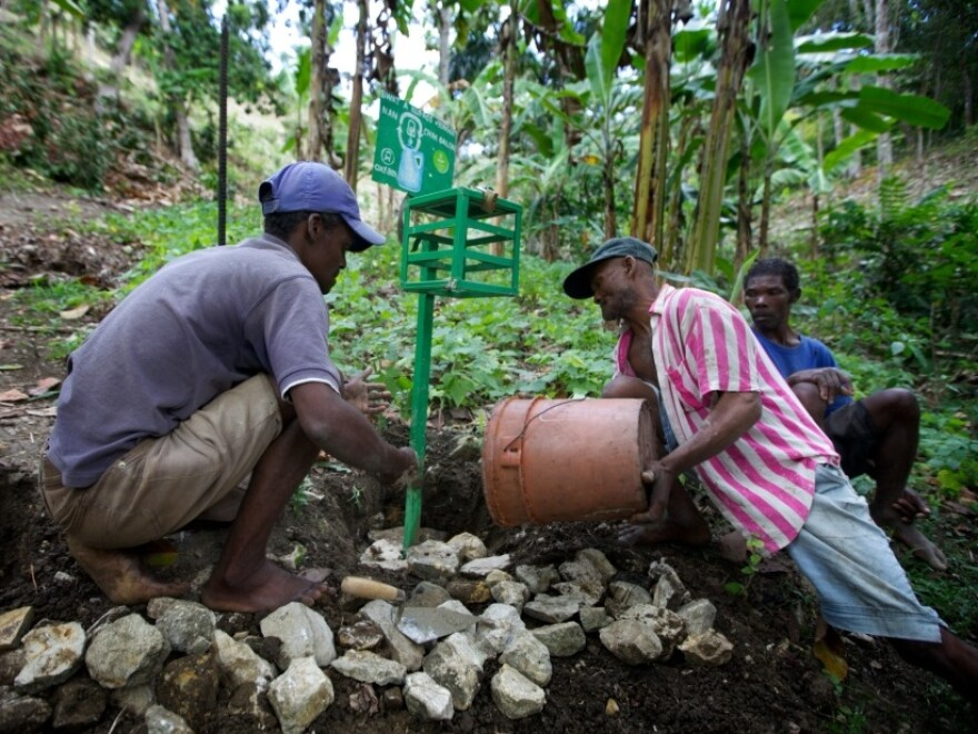 """Men in the hillside village of Font de Liane in Haiti install a """"chlorine box,"""" a dispenser that adds just the right amount of chlorine to disinfect a five-gallon bucket of water. Cholera bacteria infect many streams in Haiti that people use for drinking, bathing and washing clothes."""