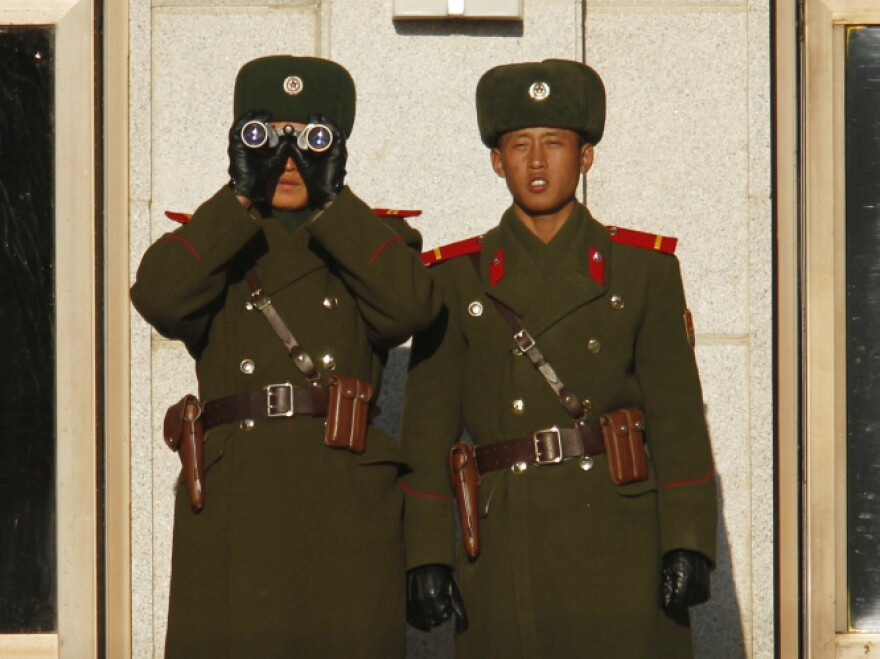 North Korean soldiers watch the South Korean side of the demilitarized zone on Thursday. North Korea has tightened security and put troops on alert since the announcement of Kim's death.
