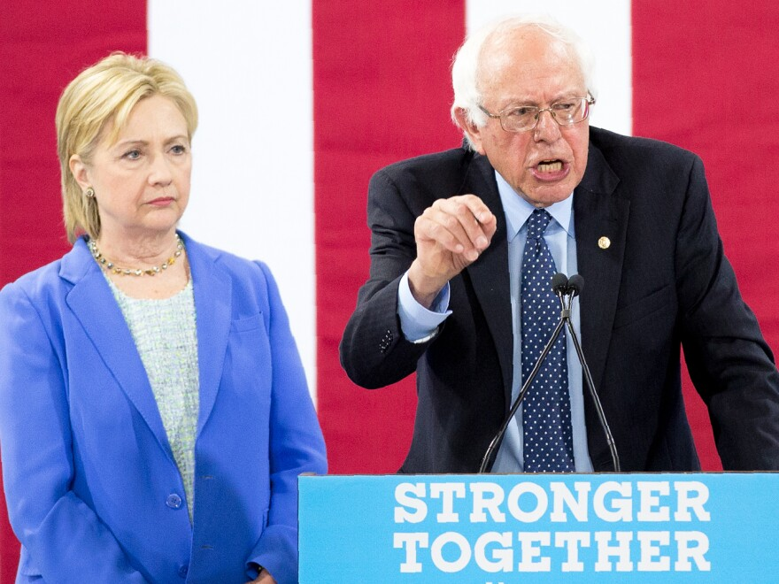 Hillary Clinton listens as Bernie Sanders makes remarks during a unity rally in July 2016 in New Hampshire.