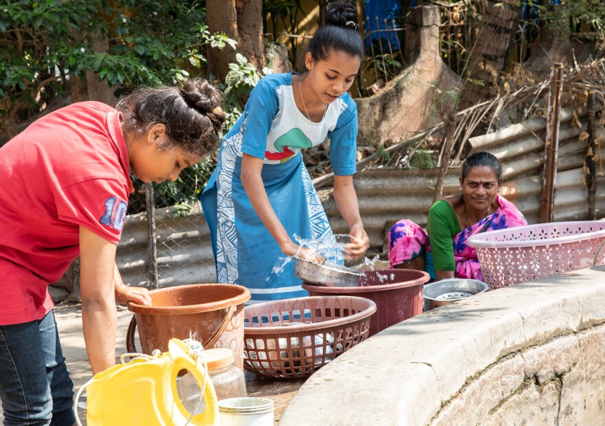 Teenager Shraddha Tandel washes cooking utensils at a communal village well.